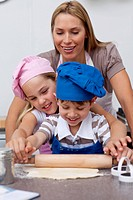 Mother and children baking cookies in the kitchen