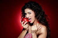 Young woman biting an apple and gesturing
