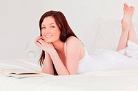 Attractive red_haired woman reading a book while lying on her be