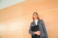 Businesswoman standing in hall against wall