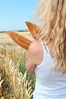 Blonde woman holding french bread in wheat field