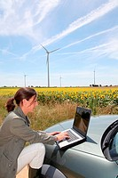 Agronomist with computer in field with wind turbines