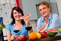 Young couple drink red wine and eat watermelon