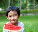 cute asian boy eating watermelon on the grass