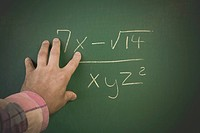 Man´s hand on a blackboard next to a math equation