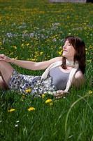 Junge Frau im Kleid genießt den Frühling auf der Wiese
