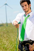 Green energy businessman in field hold plug