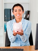 Good looking woman holding a piggy bank while looking at the cam