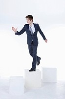businessman standing on the box and reaching out his hand