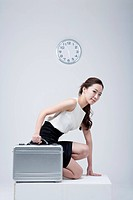 A woman about to run holding suitcase with clock background