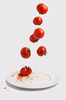 Fresh tomatoes falling on to a white plate