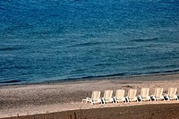 A row of empty beach loungers on a beach