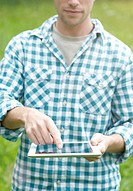 Man using a digital tablet in the countryside