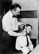 Taking Bertillon measurements. New York Police Department officer measuring a man´s ear. He is taking measurements for the identification system devel...