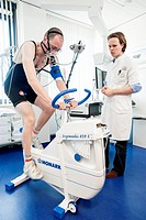 Physical fitness test. Athlete riding an exercise bike while his oxygen consumption is measured with a face mask. Electrodes on his chest monitor his ...