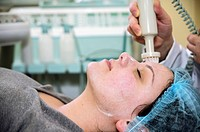 Facial brush is moved over the skin of the face in an adult female patient as part of a beauty treatment. The brush removes excess oil, dirt and dead ...