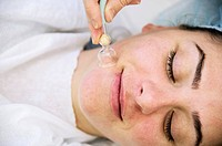 Vacuum generating device with a suction cup is applied to the skin of the face in an adult female patient during a beauty treatment. The device massag...
