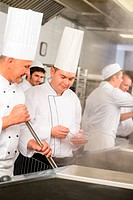Two male cook work in professional kitchen