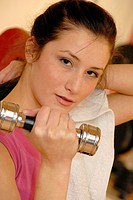 Weightlifting  Woman lifting a dumbbell during a weightlifting session in a gymnasium