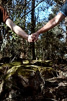 Two men holding hands in the woods