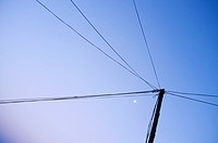 power lines and moon on blue sky