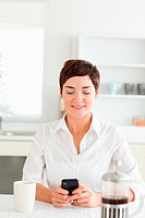 Woman with mobile phone and coffee in kitchen