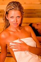 Sauna two women relaxing sweating covered towel