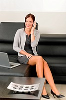 Elegant businesswoman on leather sofa call phone