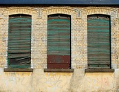 detail of 3 windows in an abandoned industrial building