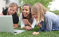 Three middle school students watch a funny video outdoors on a laptop computer and laugh.