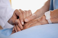 Closeup of doctor holding patient's hand