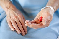 Closeup of hands holding pills.