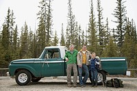 Three generations of men standing by old truck