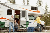 Couple relaxing with wine by camper.