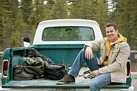 Handsome man sitting on tailgate of old truck (thumbnail)