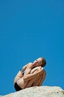 Preteen girl in bikini crouching on rock with eyes closed
