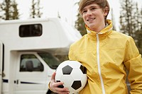 Teenager with soccer ball at campground