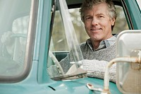 Portrait of middle_aged man sitting in old truck