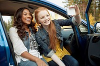 Young women laughing and taking self_portrait in car