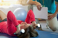 Personal trainer assisting woman with weights
