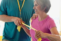Personal trainer assisting middle-aged woman (thumbnail)