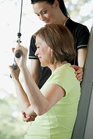Trainer assisting woman with weight training