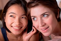 Two young women listening to cellphone together