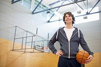 Male college student in gym with basketball (thumbnail)