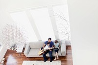 Father with children 6-7, 2-3 playing guitar at home (thumbnail)
