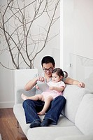 Father with daughter 2_3 sitting on sofa and using digital tablet