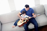 Father and son 6-7 playing guitar while sitting on sofa (thumbnail)