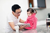 Father showing daughter 2-3 digital tablet (thumbnail)