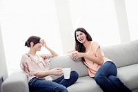 Friends sitting on sofa and talking