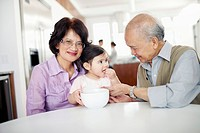 Grandparents and granddaughter 2_3 eating breakfast in kitchen
